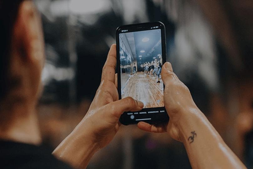 Mujer prepara su smartphone para grabar una clase de entrenamiento en vivo