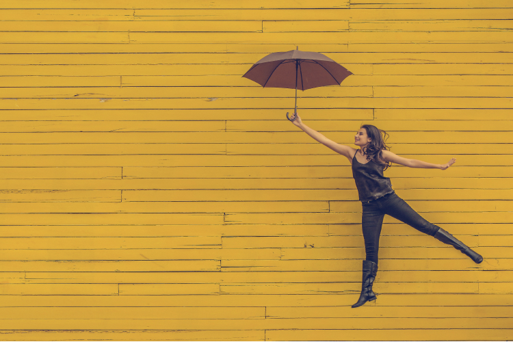 Woman jumps with umbrella on yellow background