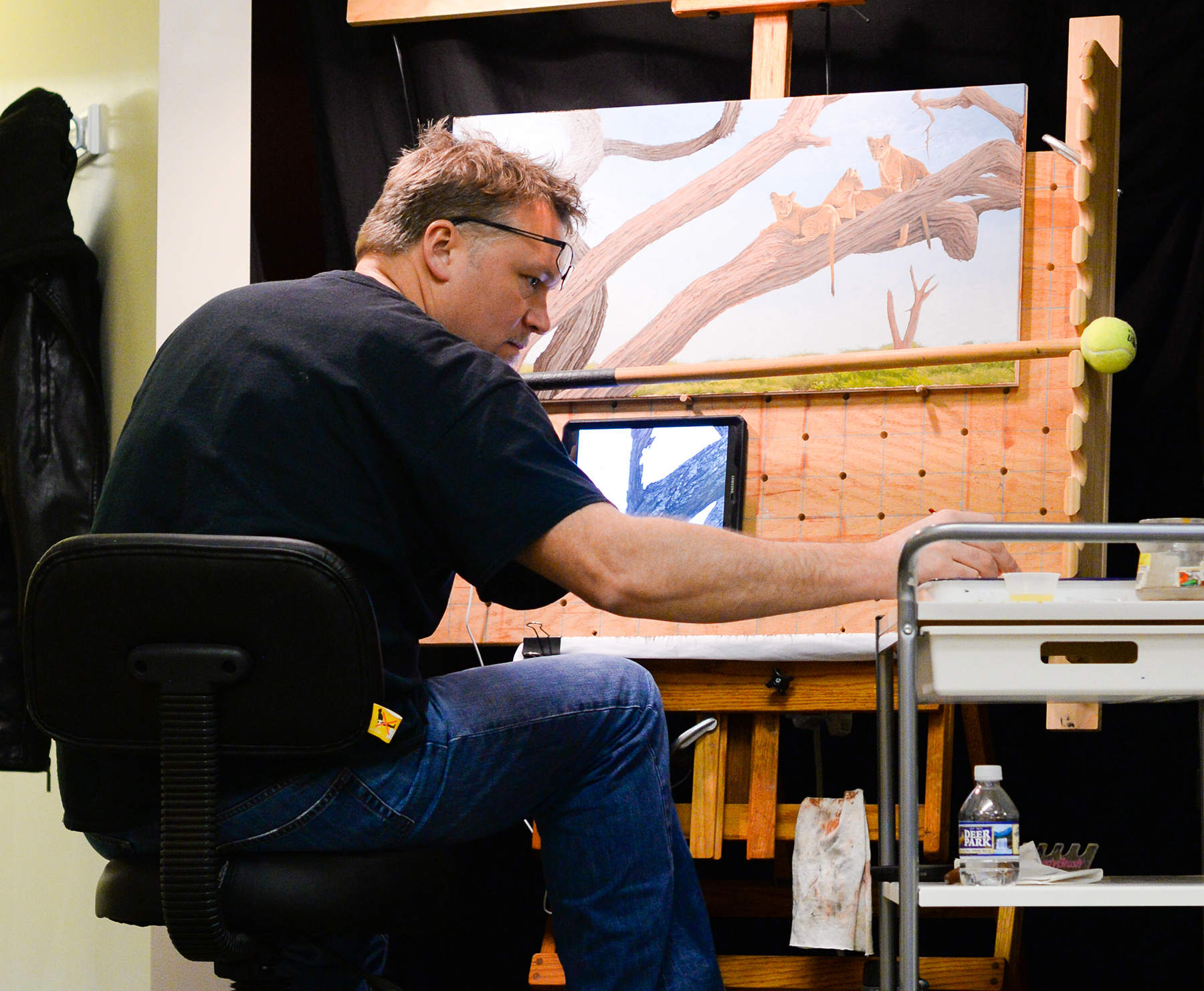 Artist Robert Louis Caldwell working on a oil painting of lions