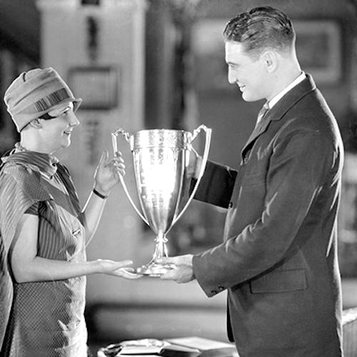 man awarding winners cup to woman