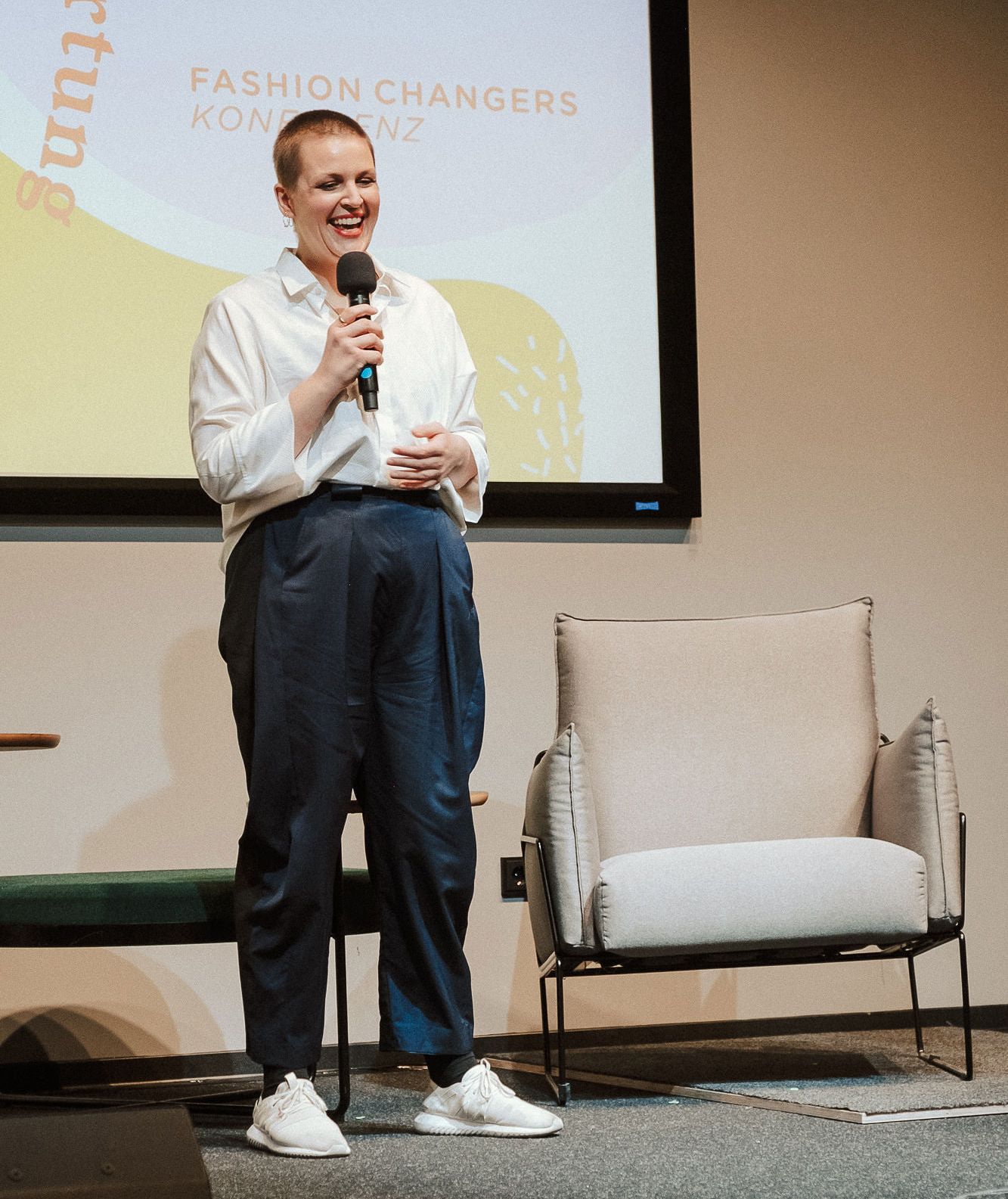 Person mit kurzen Haaren, Lippenstift, weißer Bluse und blauer Hose steht auf der Bühne der Fashion Changers Konferenz und hält ein Mikrofon in der Hand