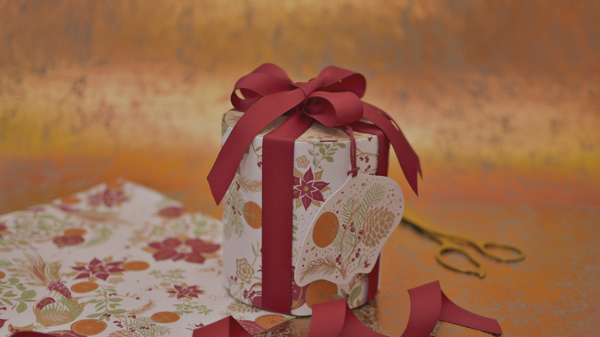 Stack of gifts wrapped in pink paper with red ribbon.