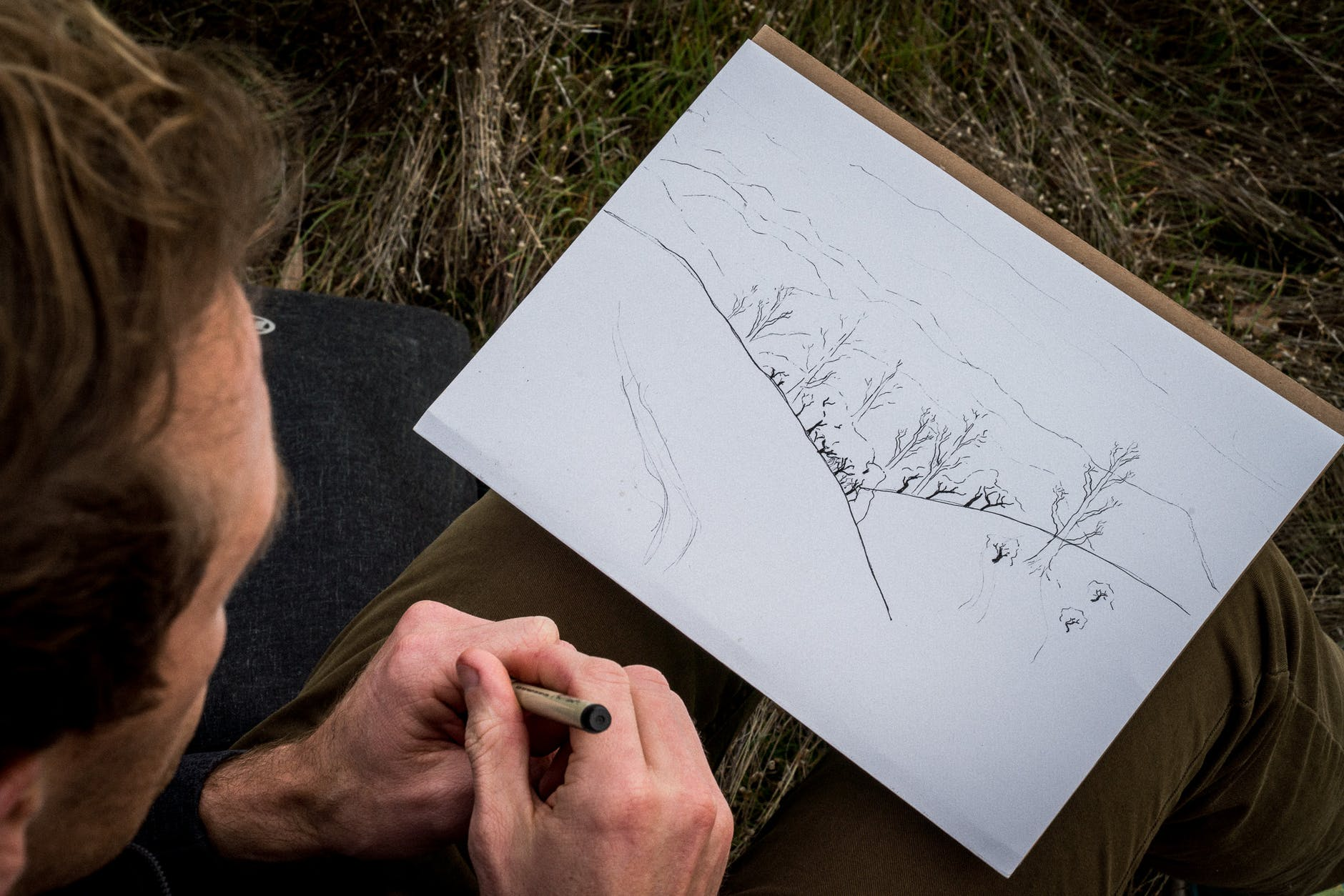 Man looking at his drawing of the landscape while sitting outside