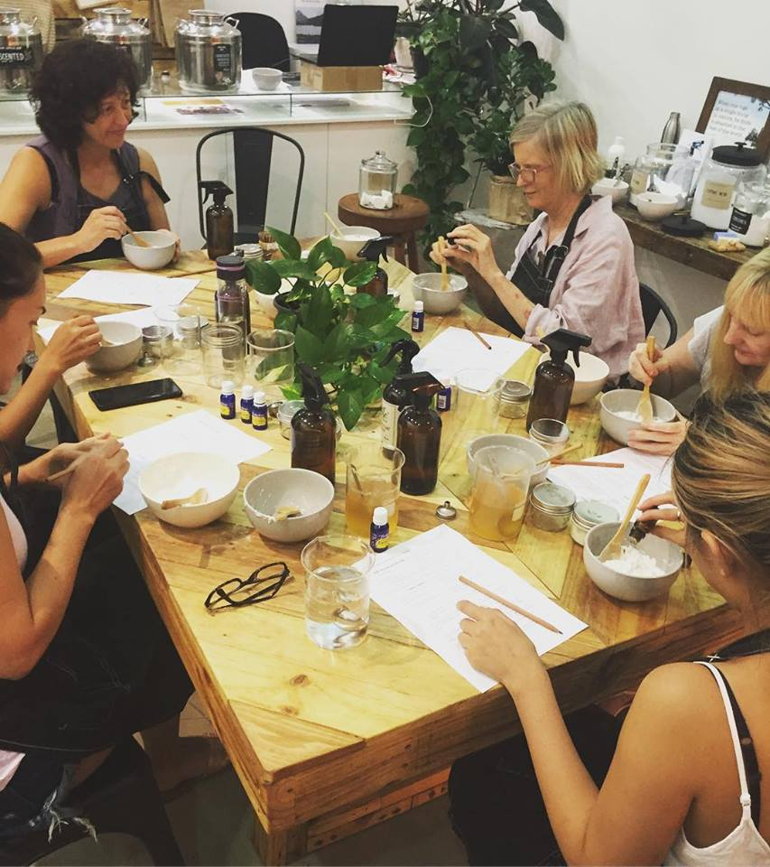 Group of people sitting around a table making natural skin care