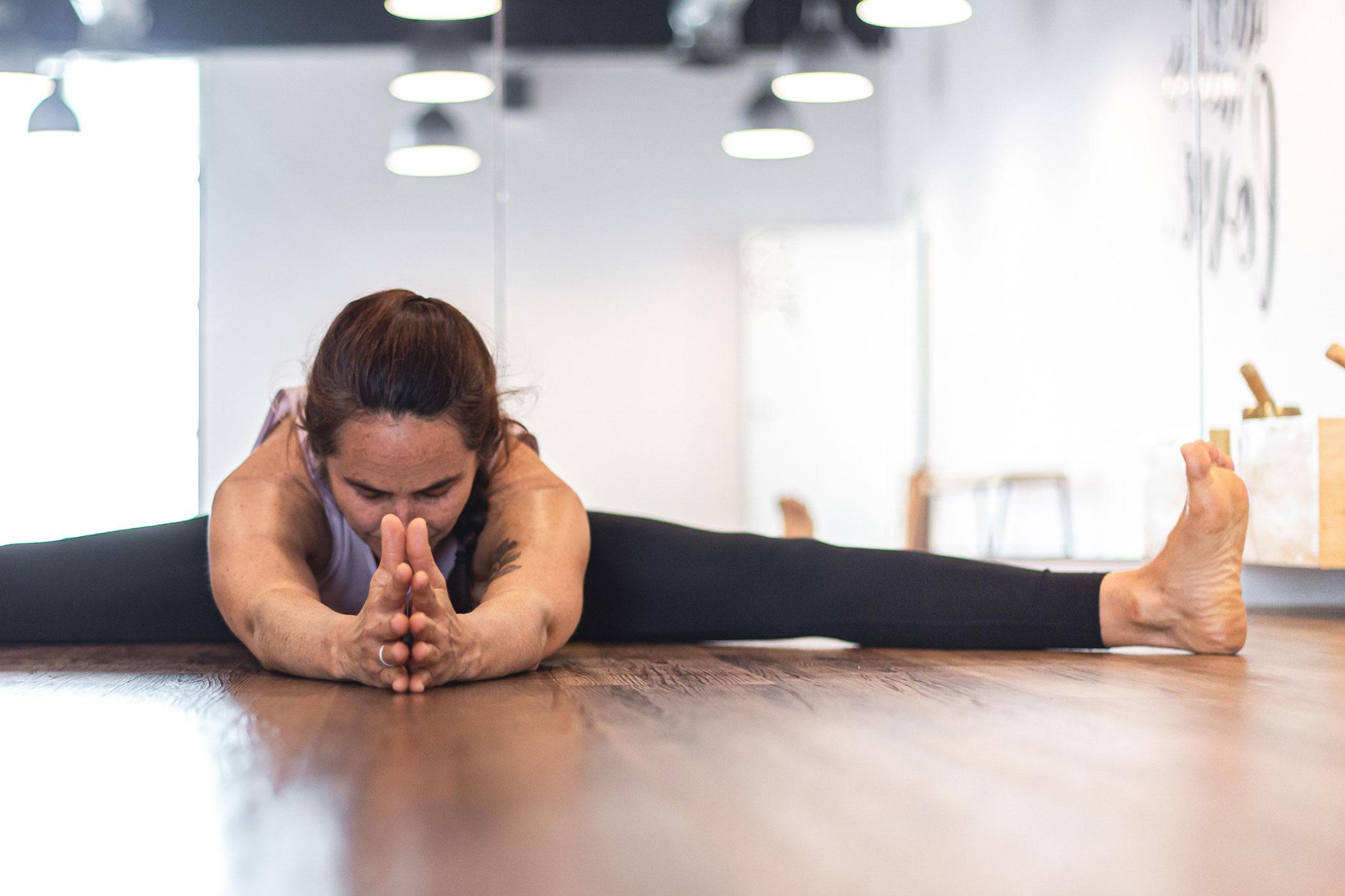 Mujer practica yoga en una postura de torsión y desintoxicación.