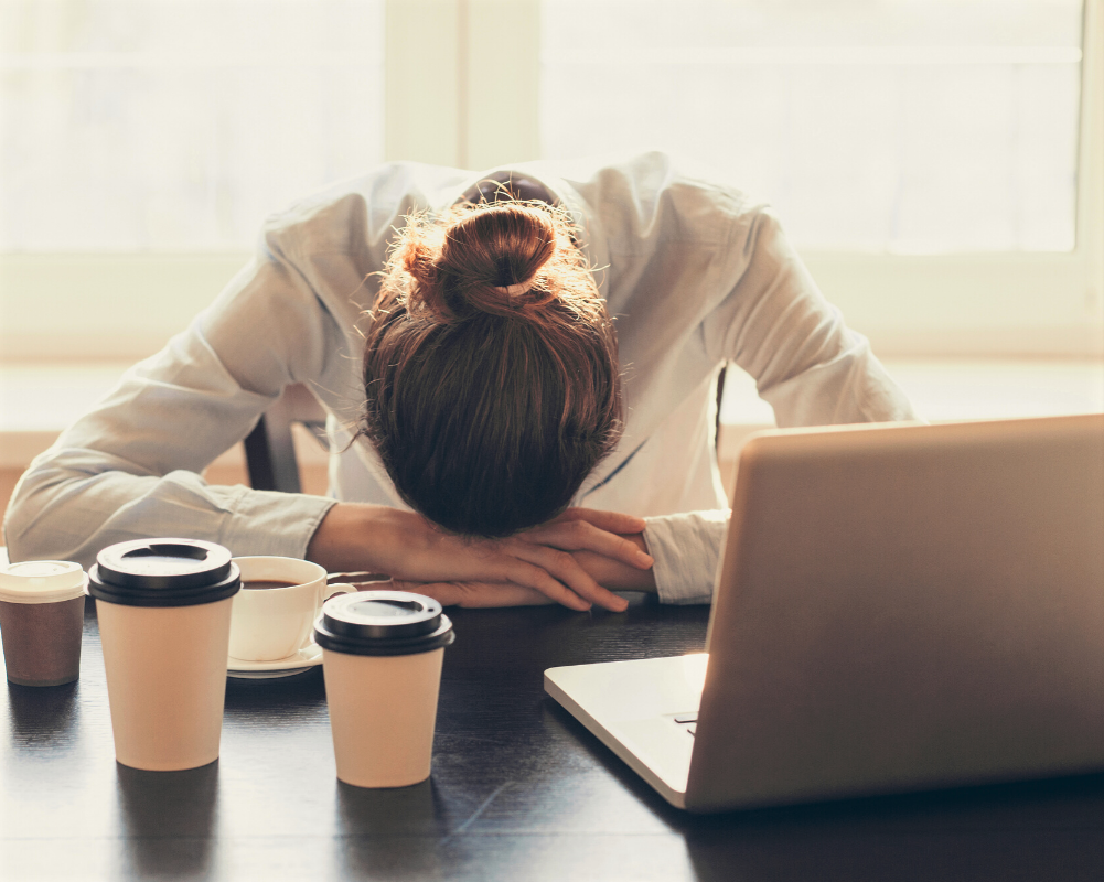 tired woman with head down next to her laptop and four cups of coffee