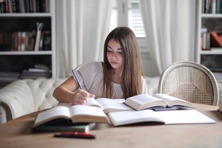 girl writing and reading school books
