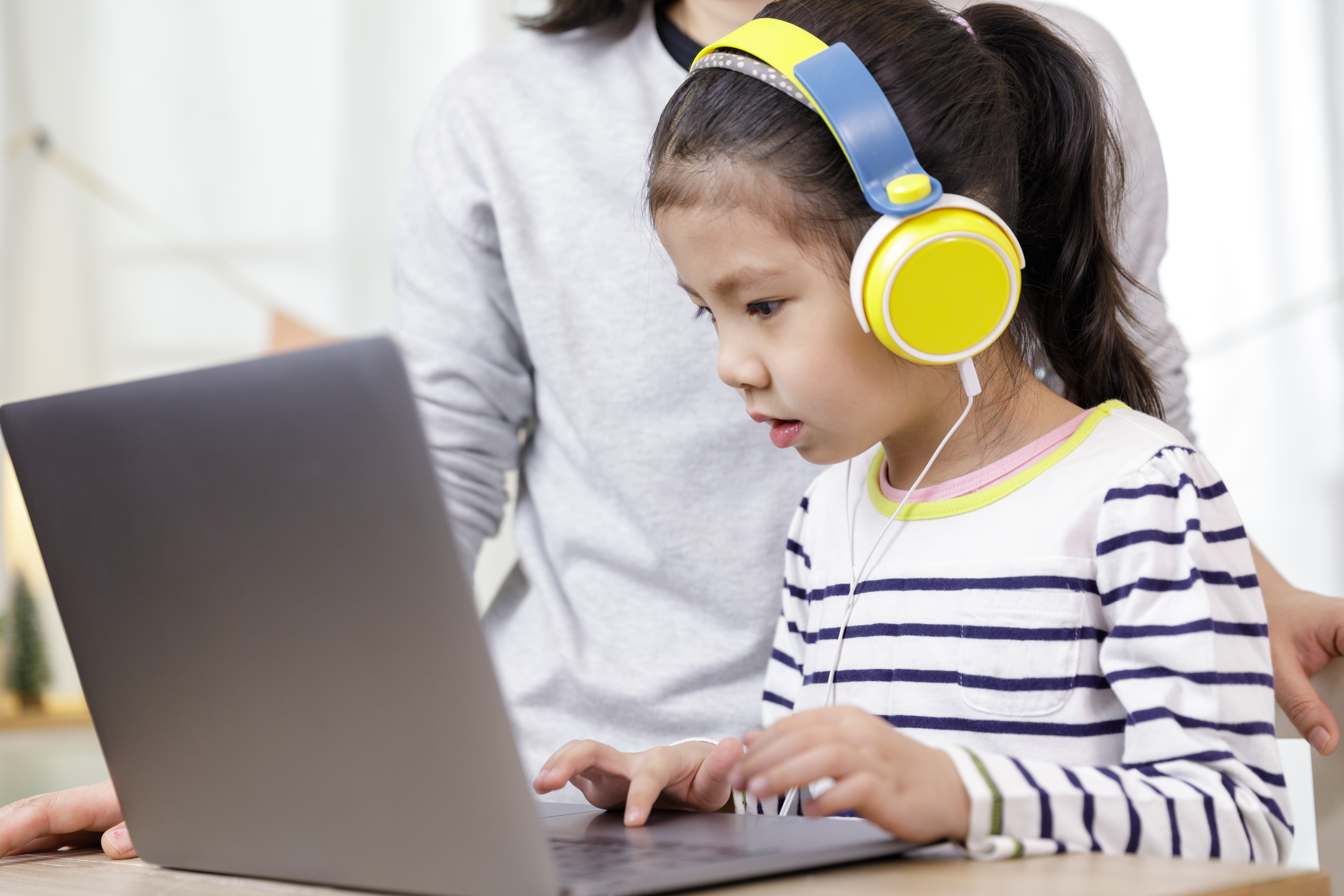 a small child completes an activity on a laptop computer. She wears large yellow headphones.