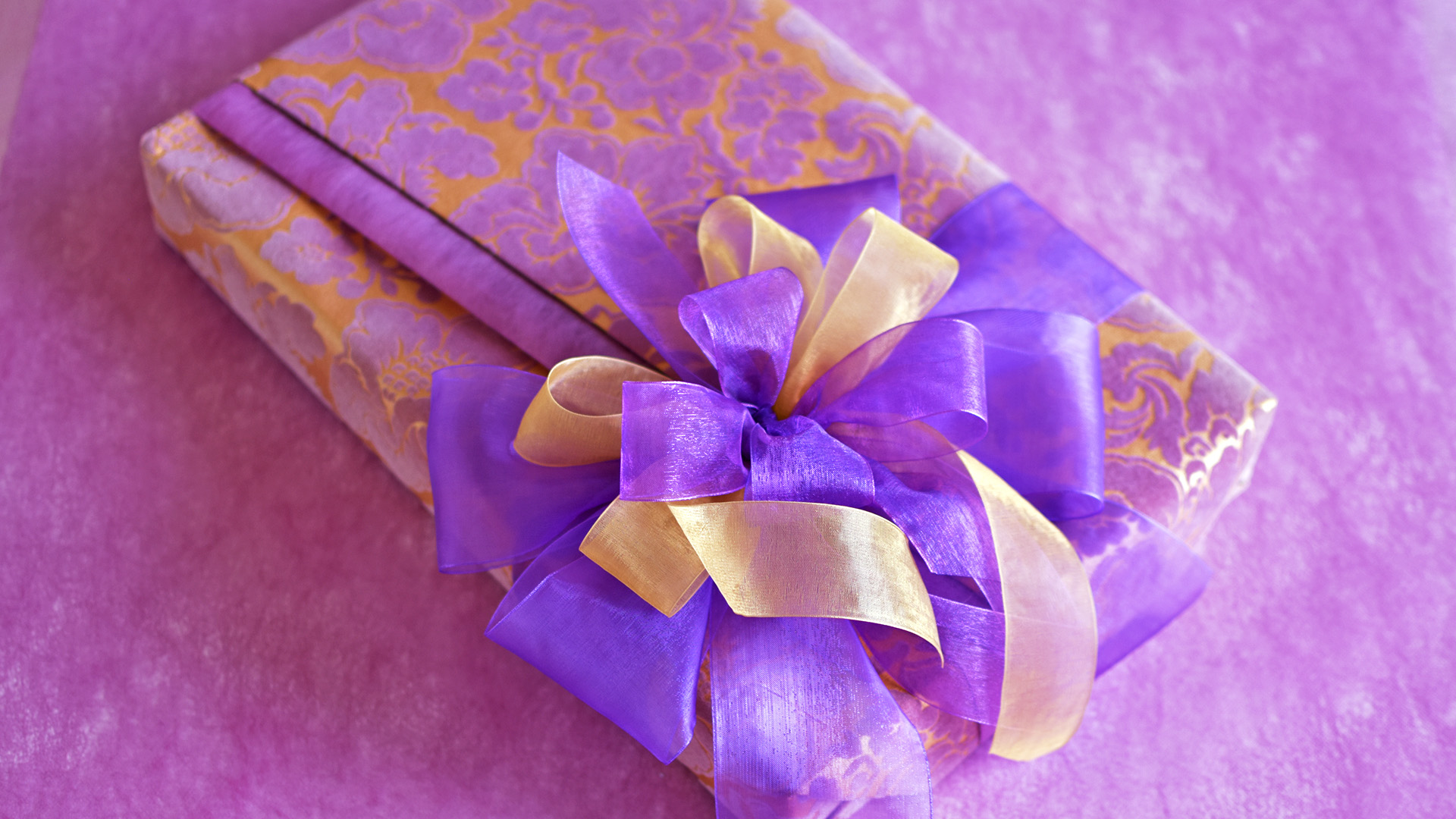 Gift wrapped in a blue paper with golden pattern, with a golden ribbon bow and white roses decorations.