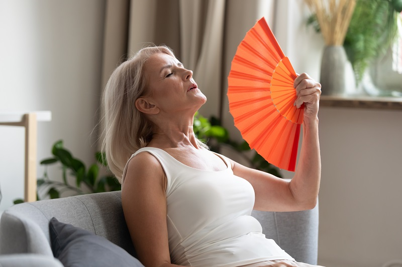 Menopausal women fanning herself