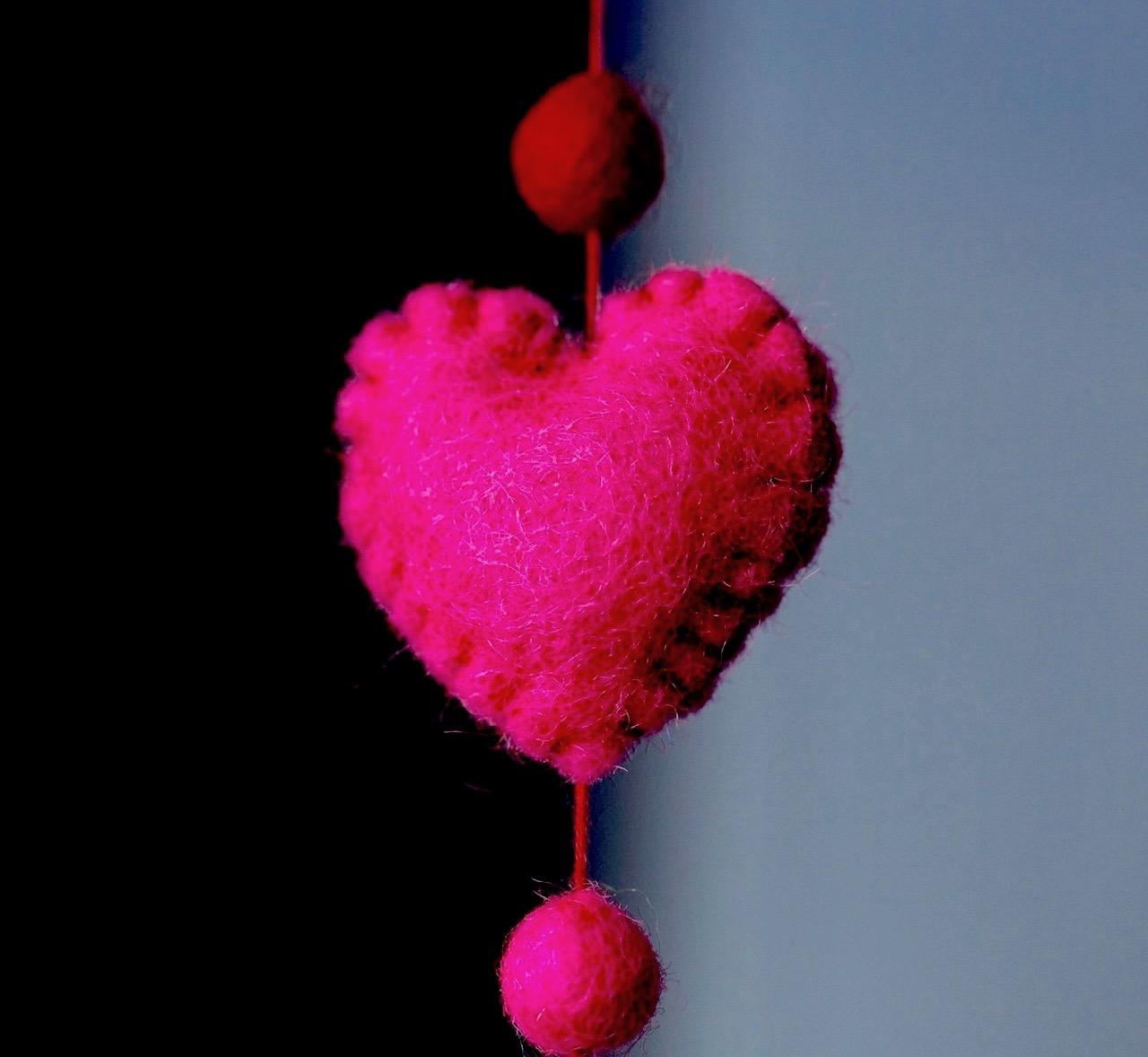 Fuschia pink heart made of felt hanging against a dark background