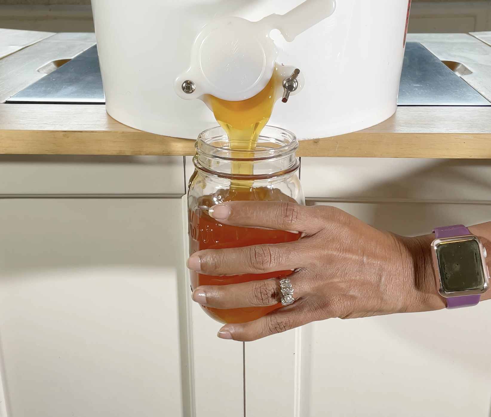 raw natural honey being poured in mason jar at home