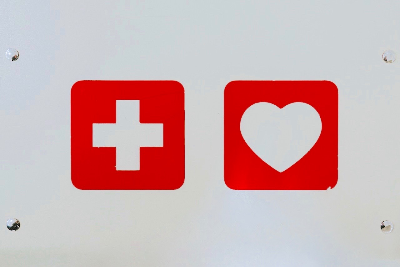 Red First Aid symbol on a white panel