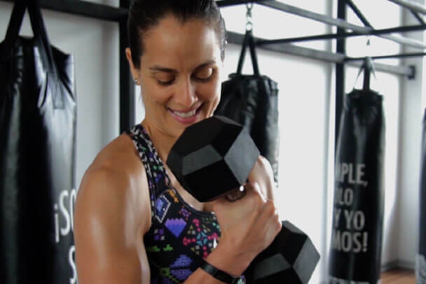 Mujer sonriente levanta una pesa y hace entrenamiento funcional frente a sacos de box