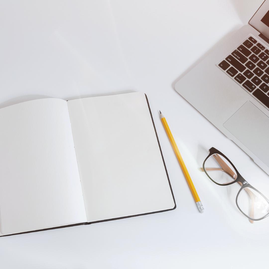 Un cuaderno blanco, un lapiz amarillo, unos lentes y una laptop sobre una mesa blanca.