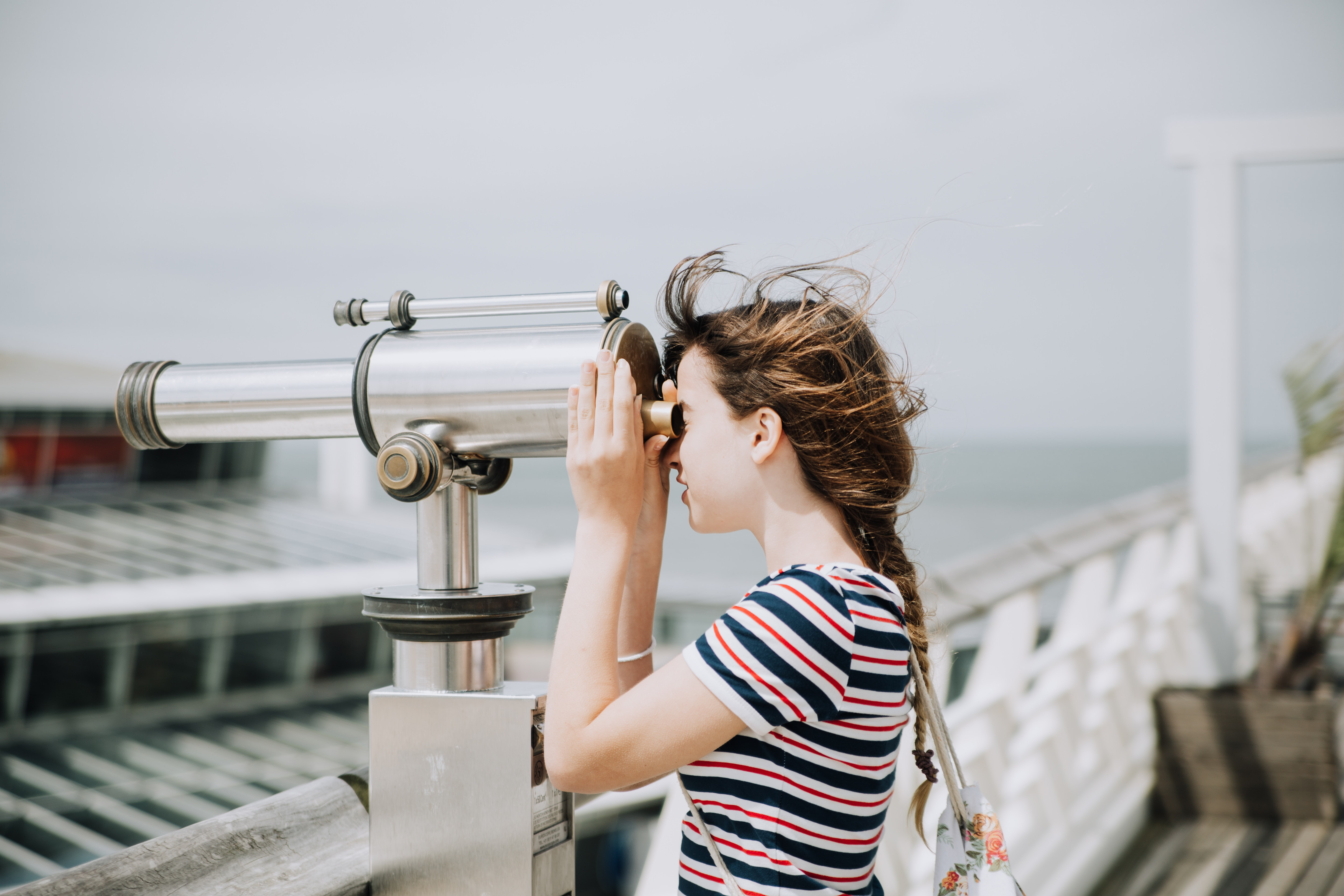Female looking through a telescope by the water