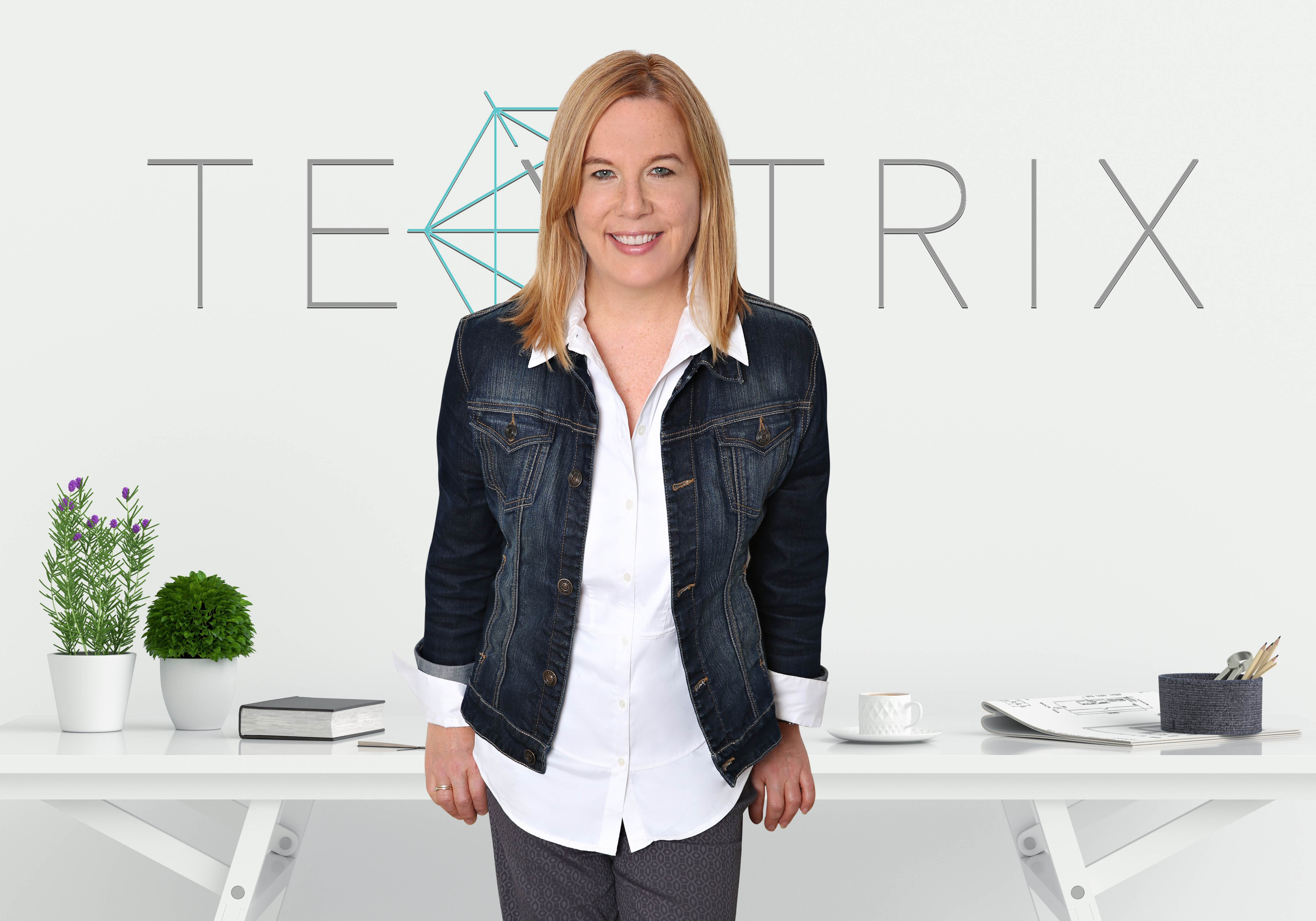 A woman with shoulder length red/blond hair stands in front of a table wearing a white shirt and denim jacket. She is smiling