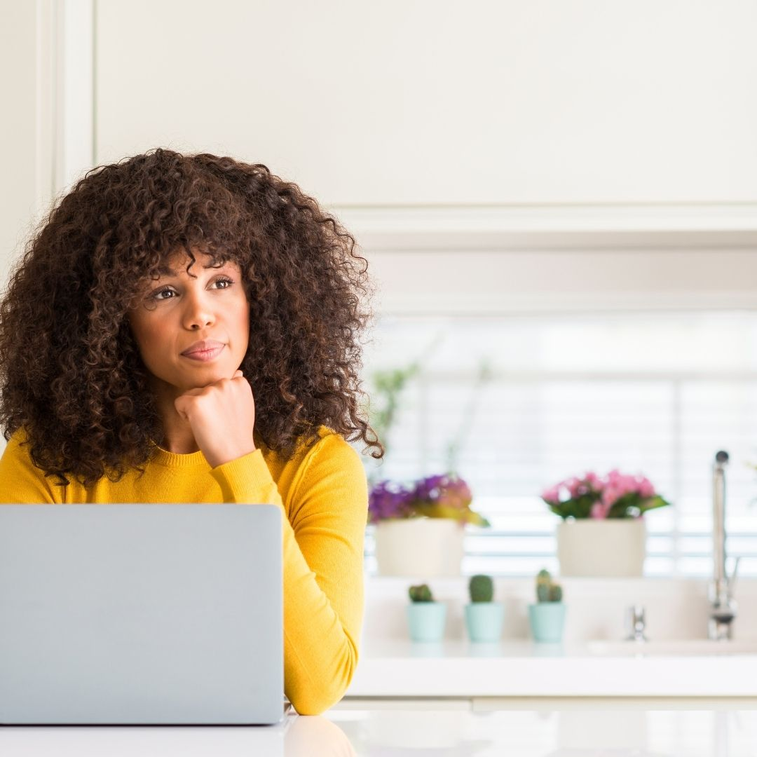 woman thinking at laptop in kitchen
