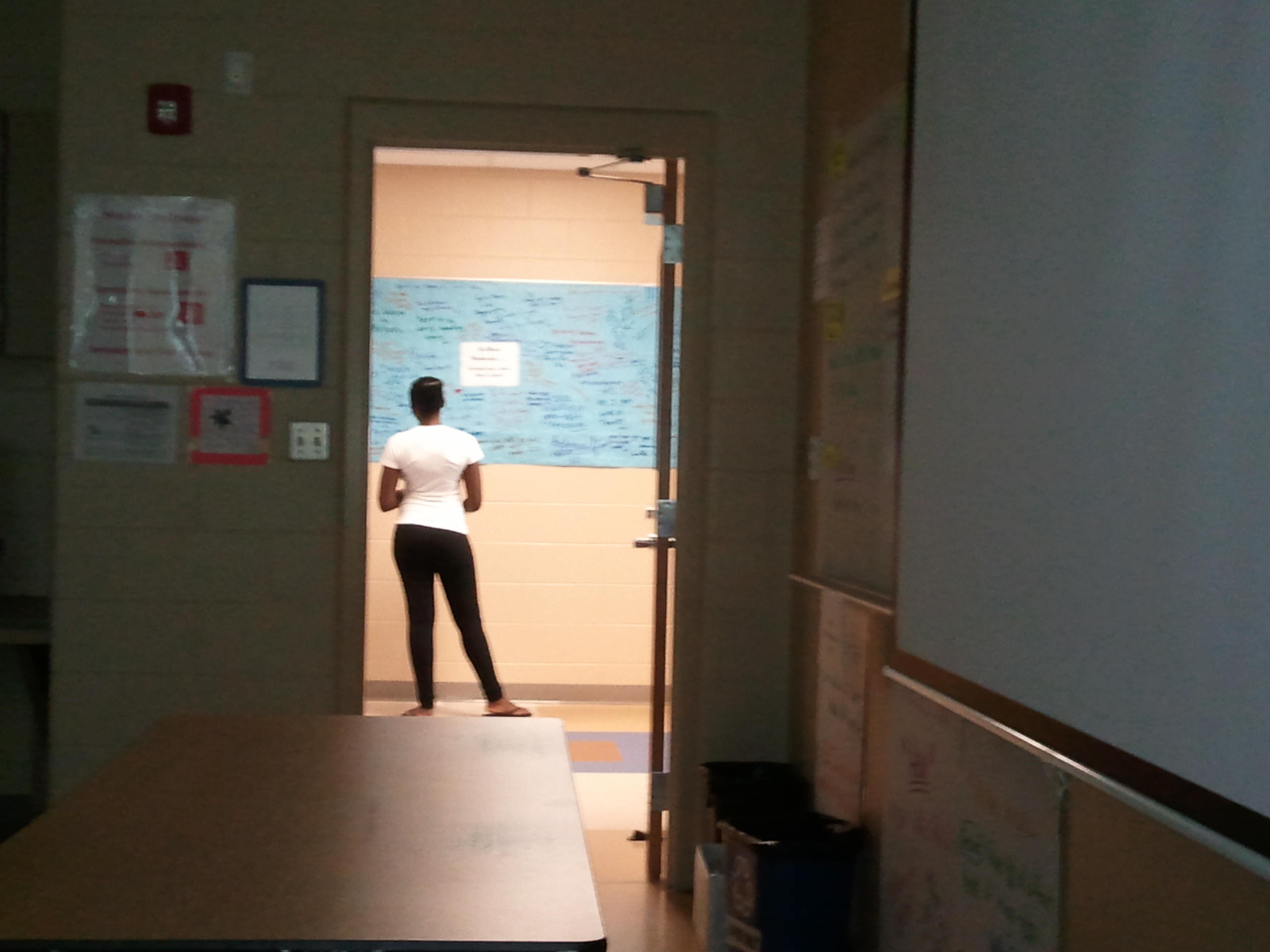 High school student standing in the hallways looks at student writing on the wall project