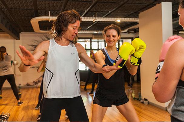 Una mujer enseña a otra las posturas correctas para boxear
