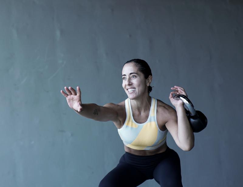 Mujer en ropa deportiva realiza ejercicios funcionales y de tonificación con un kettlebell en la mano izquierda.