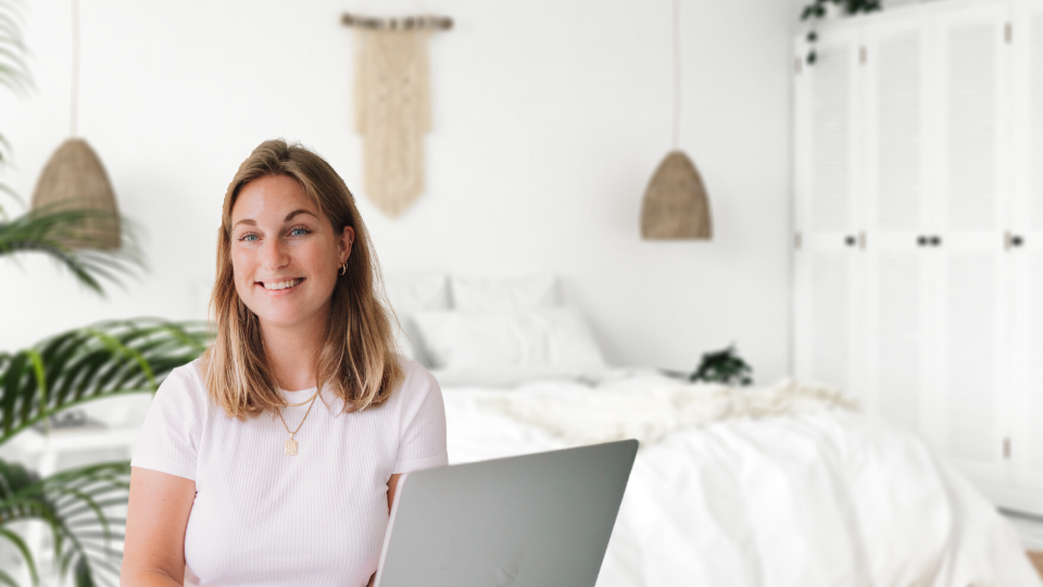 social media manager girl with laptop in white room with white bed