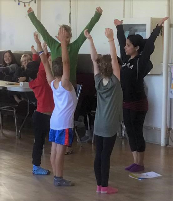 Kids Yoga Teacher Training Scavenger Hunt Game With Teacher leading children in the upward hands yoga pose
