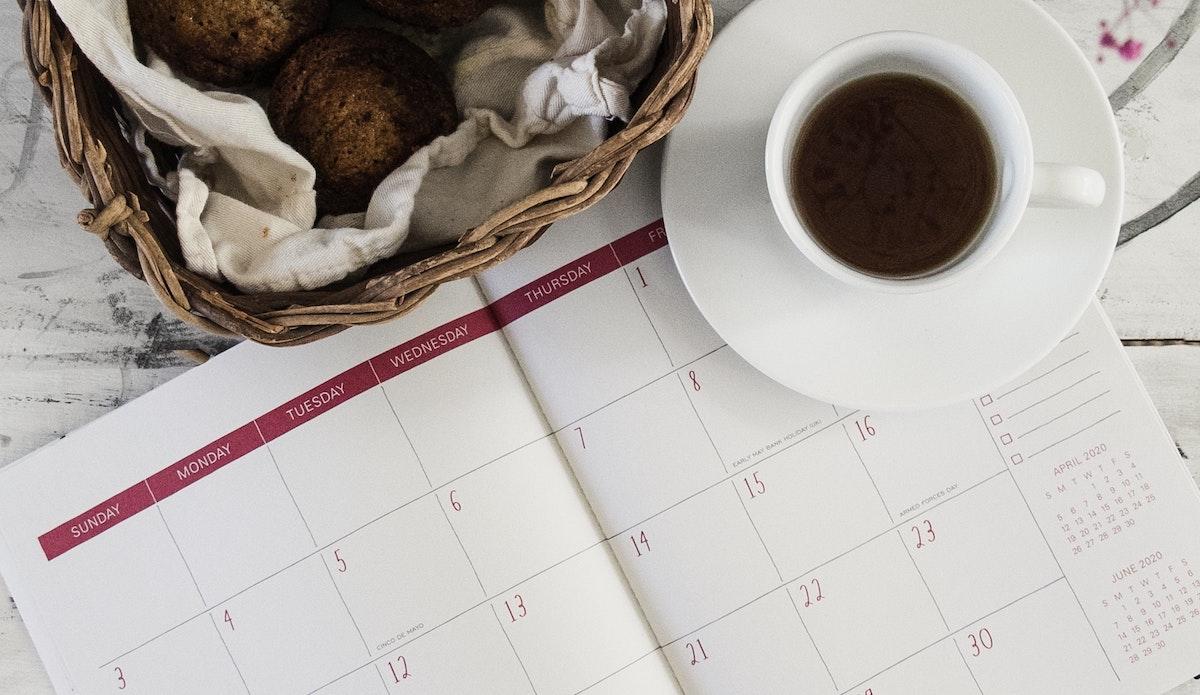 A calendar next to a cup of tea.