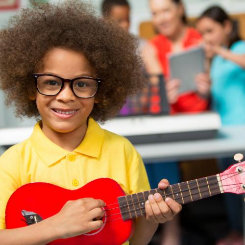 child with red ukulele