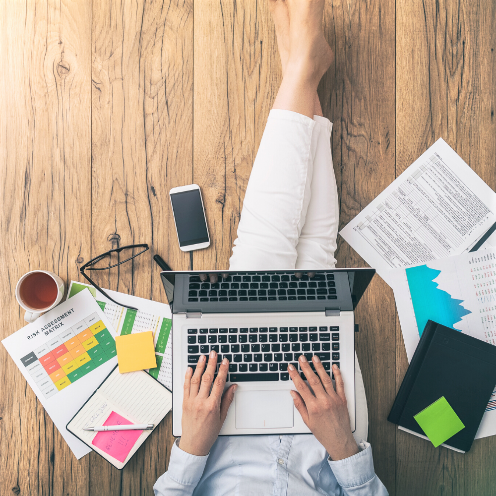 woman sitting on floor with laptop and business planning documents