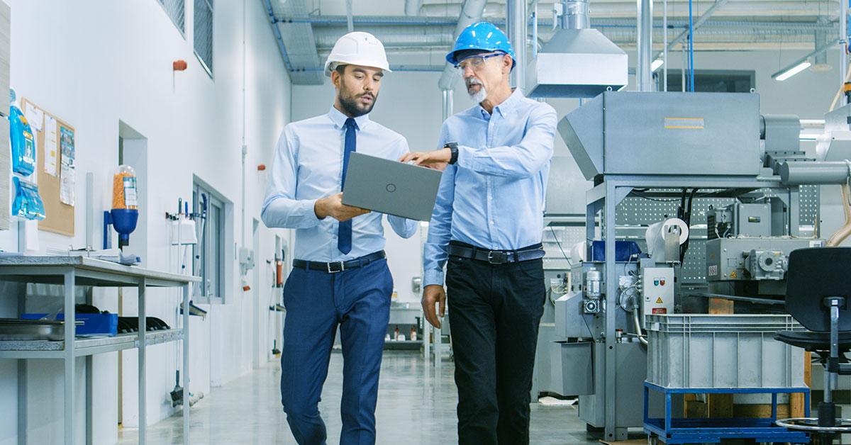 Two men walking a machine shop