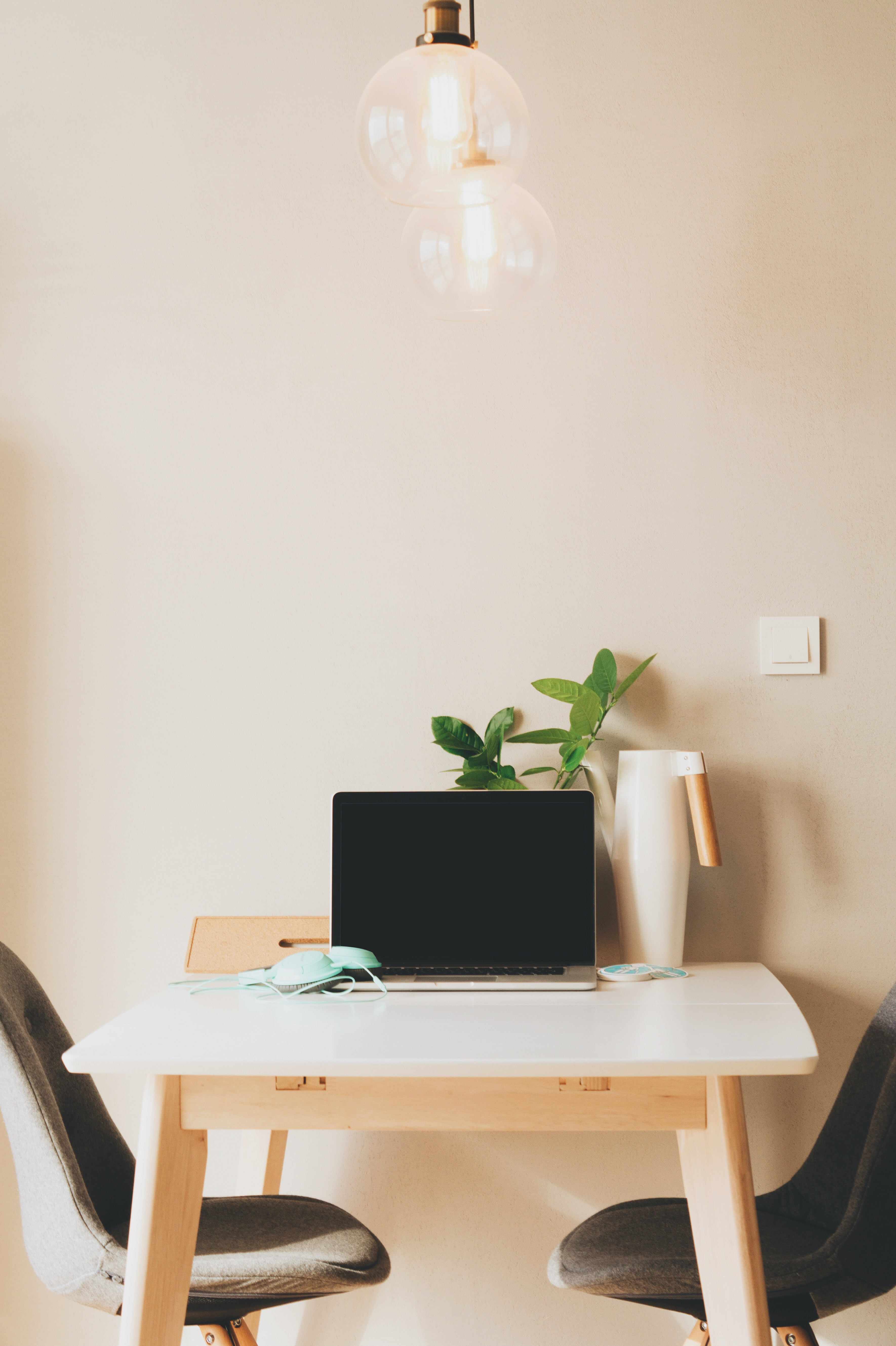 Bright light bulbs above a table with a laptop, two chairs, headphones, watering can, and a plant