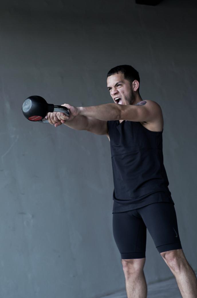 Hombre en ropa deportiva negra alza un kettlebell mientras realiza ejercicios funcionales y de tonificación.
