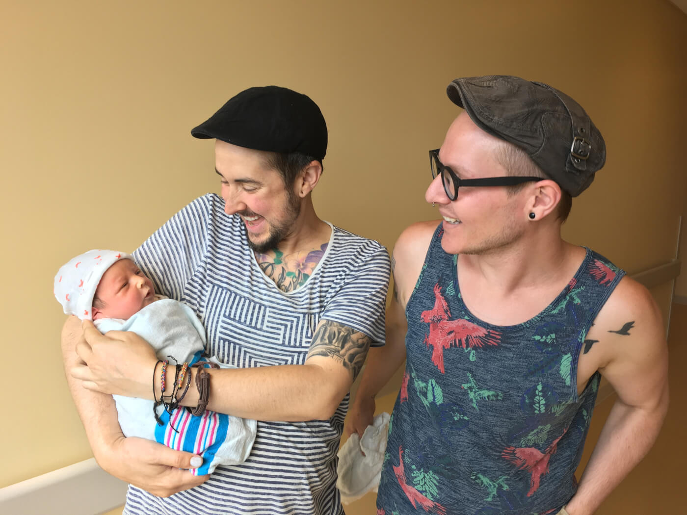 Trystan & Biff stand together smiling, Trystan holds his newborn and Biff stands beside them.