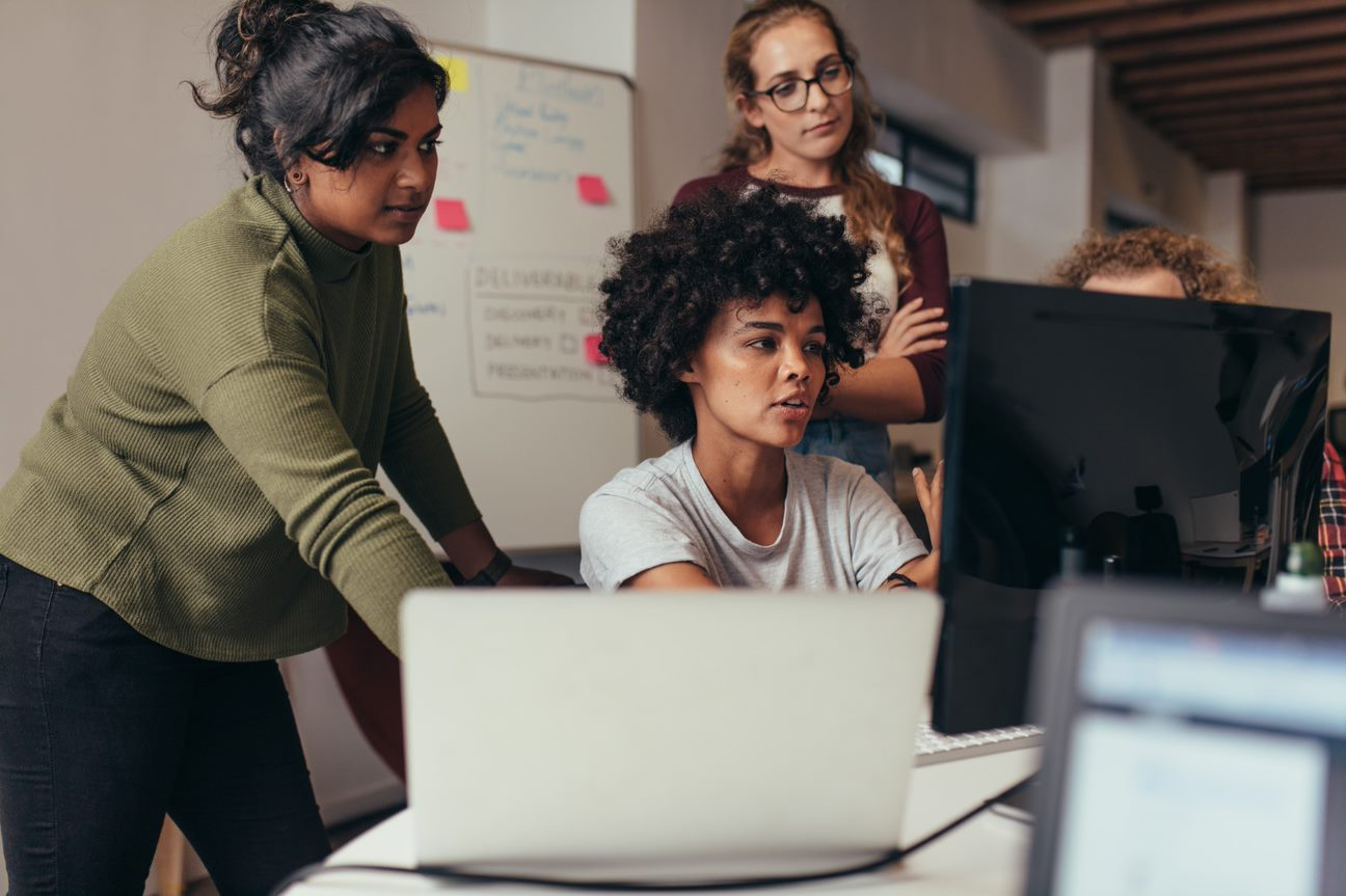 Four women looking at a computer monitor.