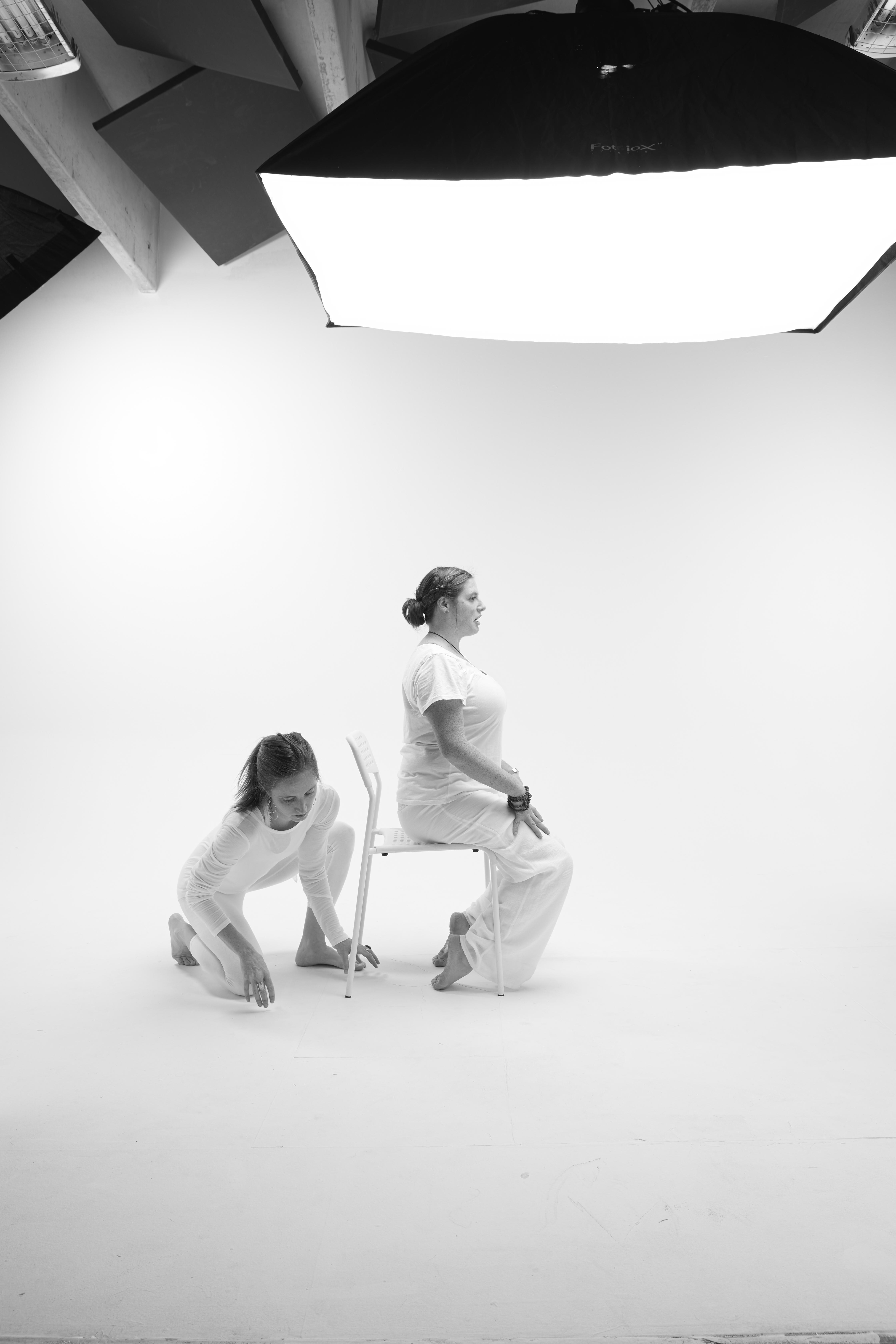 black and white image of yin yoga teacher Kaitlin Jackson demonstrating toe pose using a chair and Kari Kwinn preparing to support her