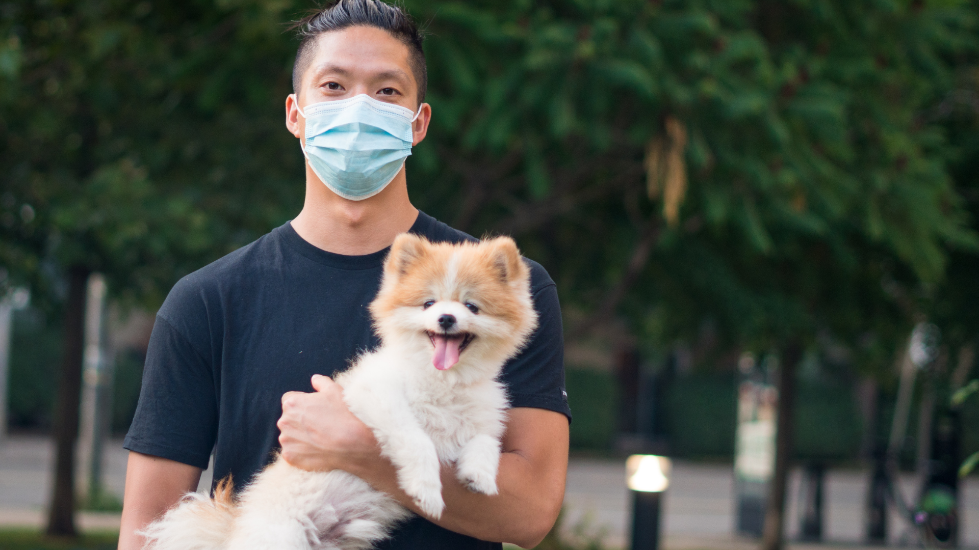 man in mask holding his pomeranian dog