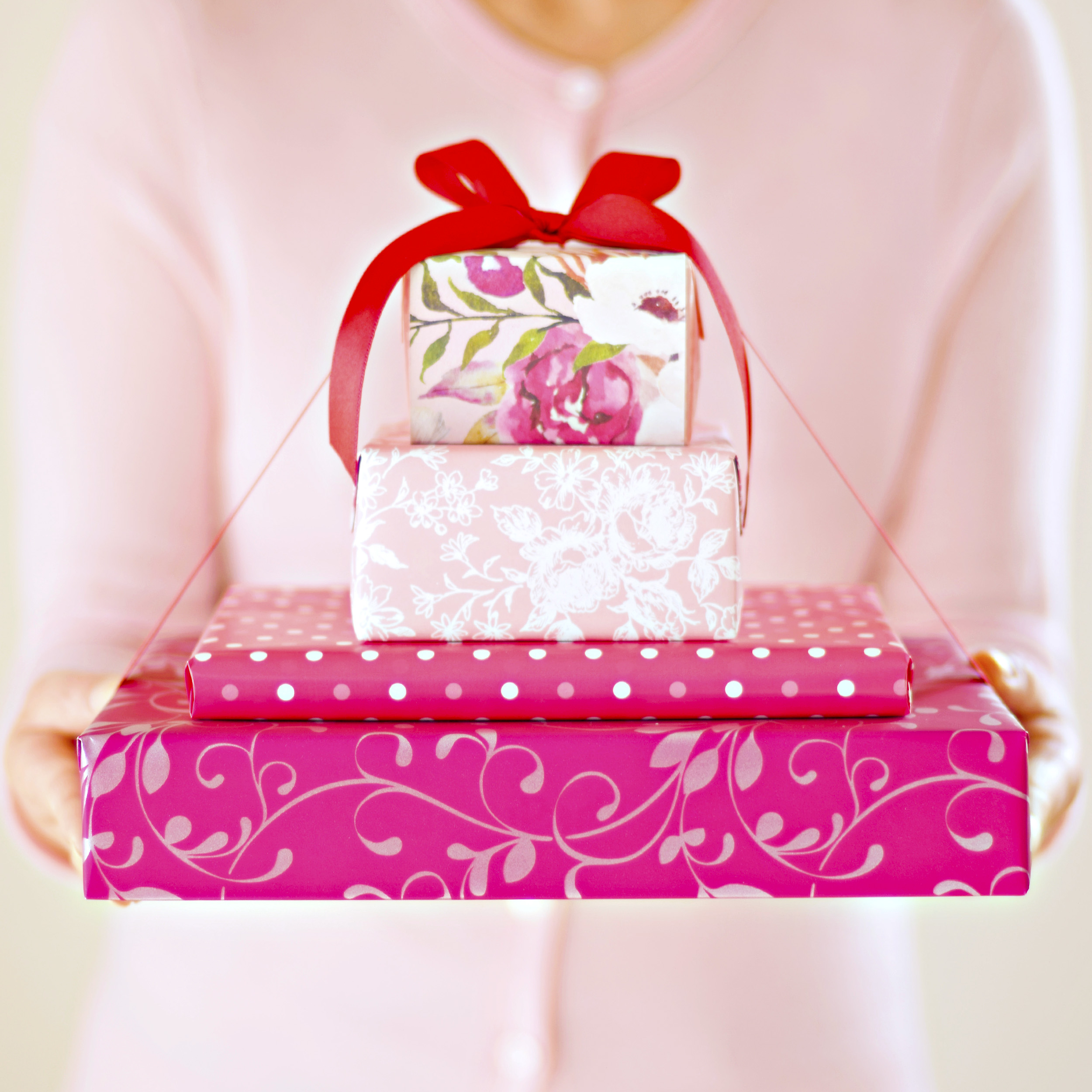 A person offering stacked gift boxes tied with red ribbon and held in both hands.