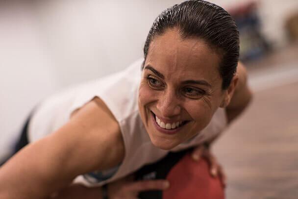 Mujer sonriente hace ejercicios funcionales con una pelota medicional.