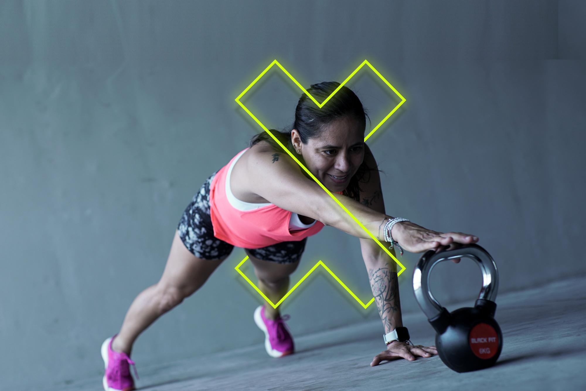 Mujer en short se ejercita con un kettlebell y hace entrenamiento funcional.