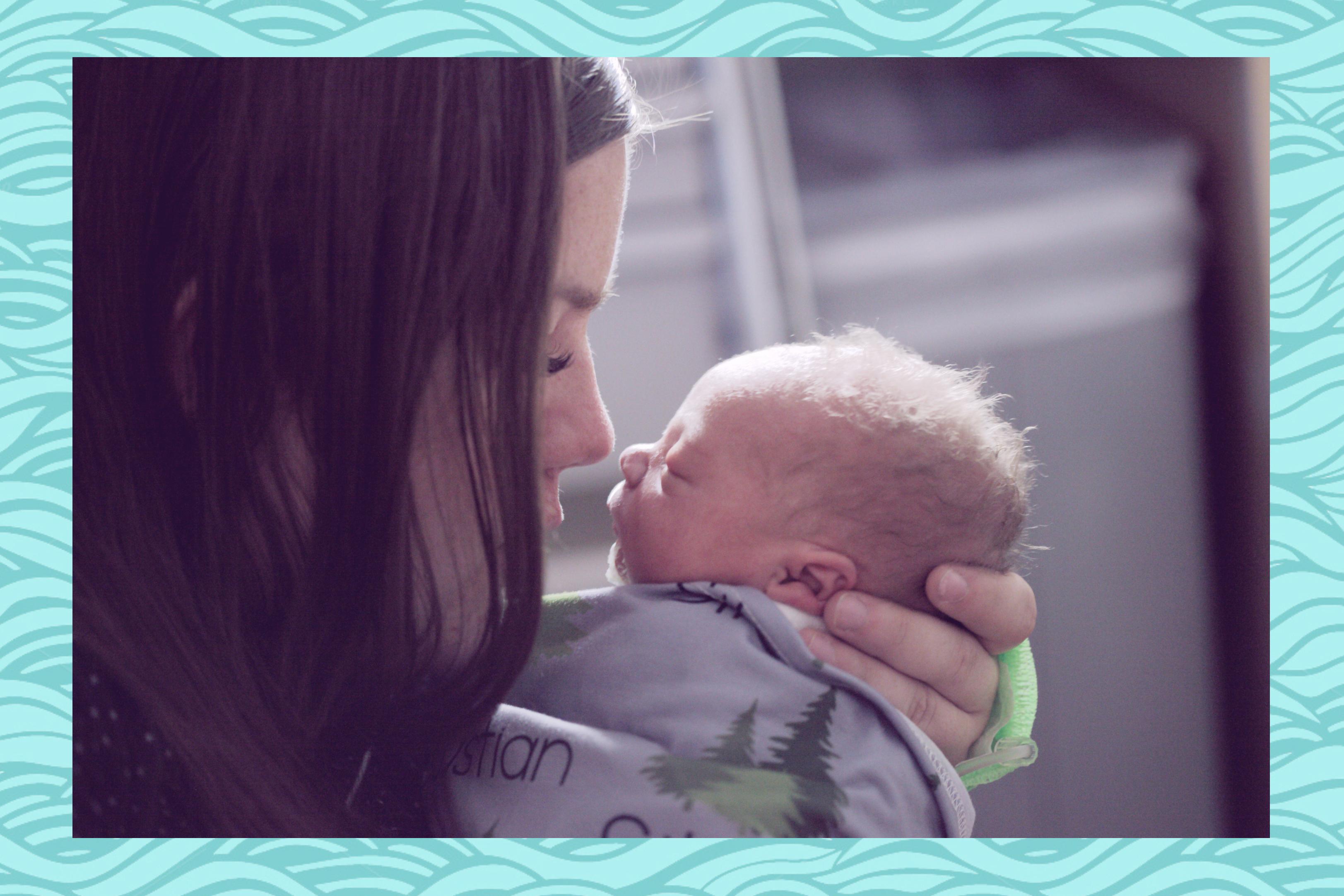 women with newborn baby in hands