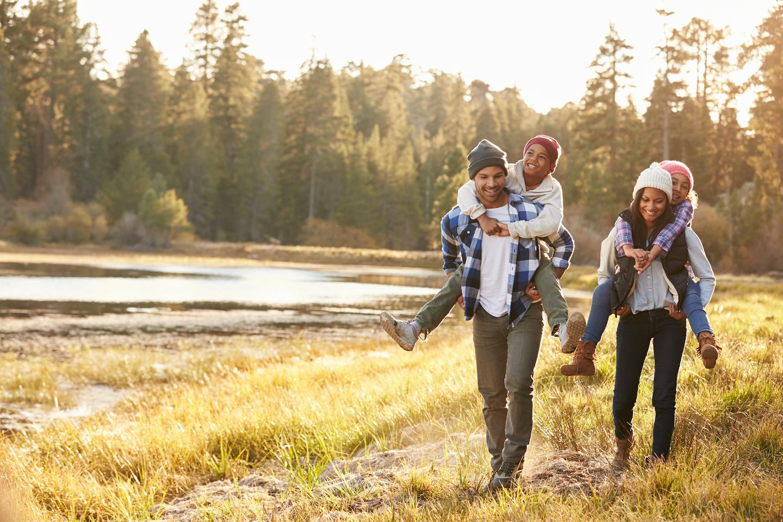 happy family hiking near beautiful pond