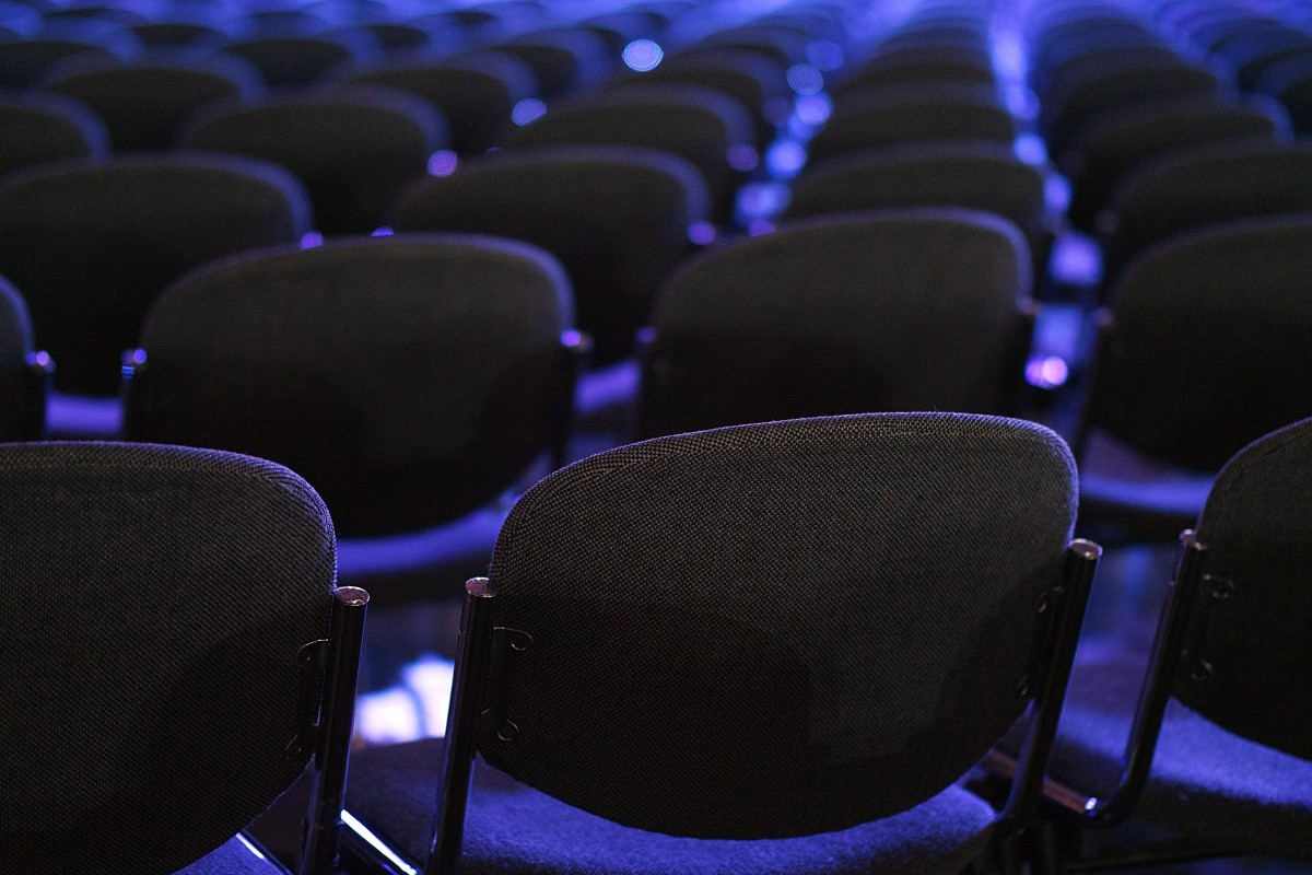 rows of black fabric conference chairs in a blue light