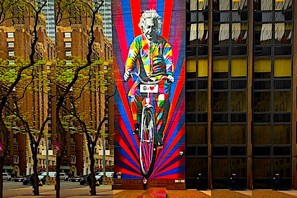 Hanging from the top of a tall building, a very large picture of Einstein riding a bicycle represents the category 'Famous People'
