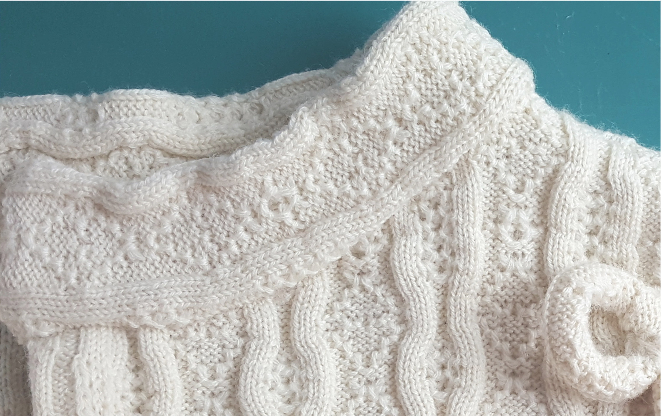 Finished novelty neckline of cream colored cardigan sweater