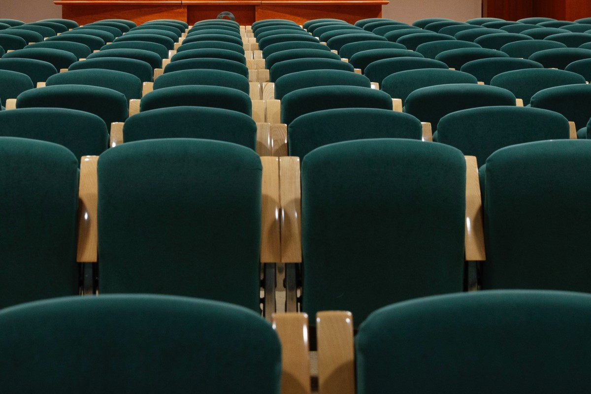 rows of green plastic venue chairs, each with a small white number