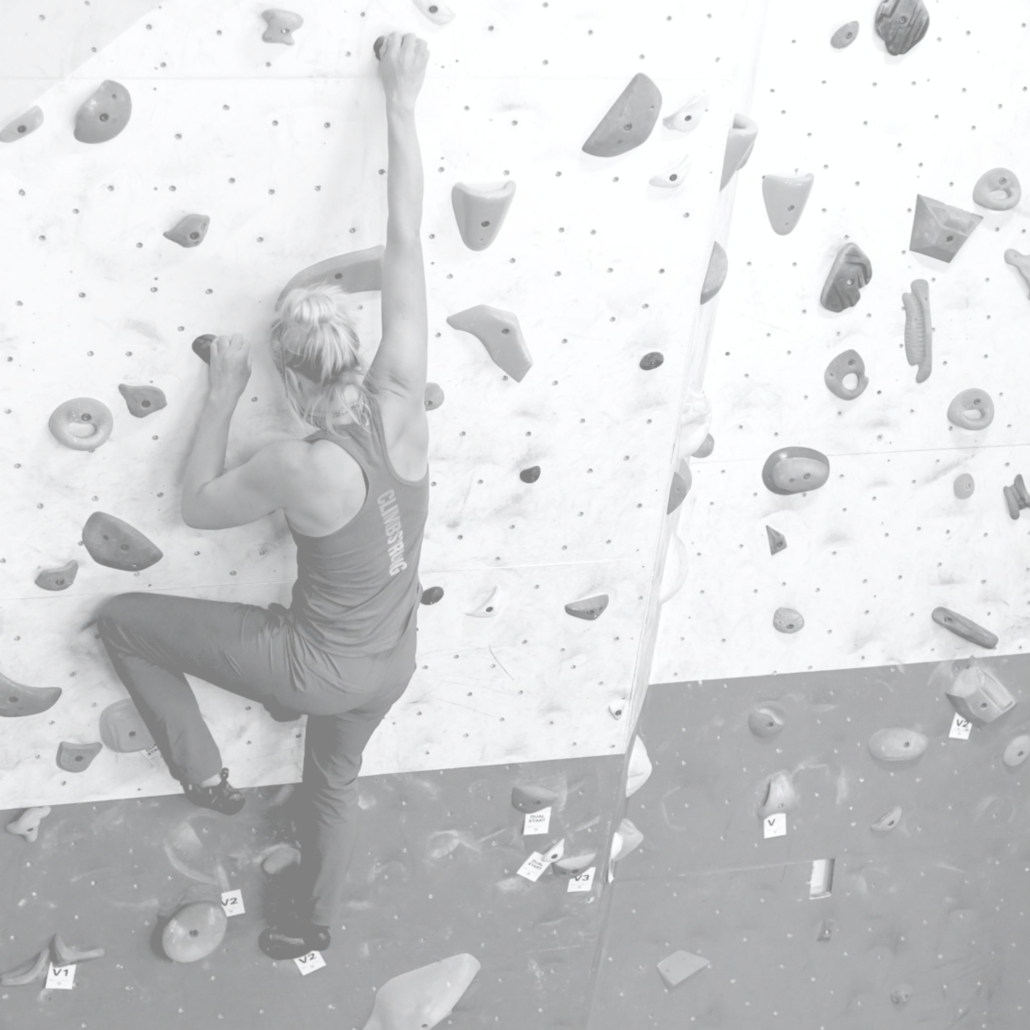 black and white photo of a woman climbing on an indoor climbing wall