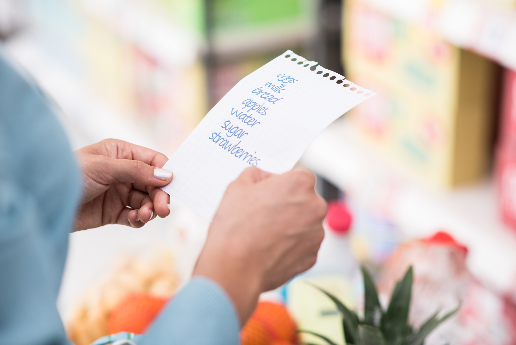 womans hands holding shopping list