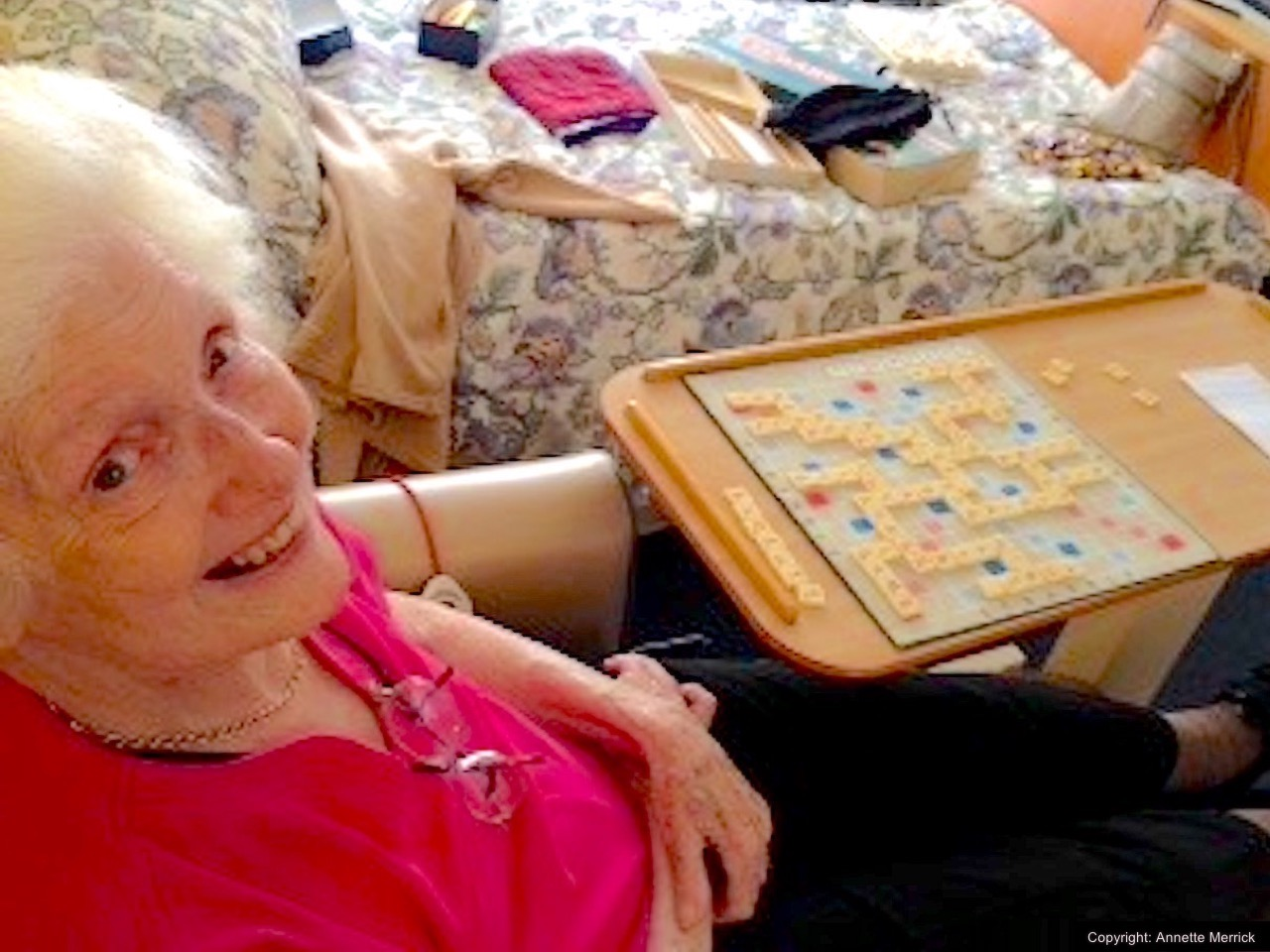 Smiling woman looking up at camera with a game of Scrabble next to her