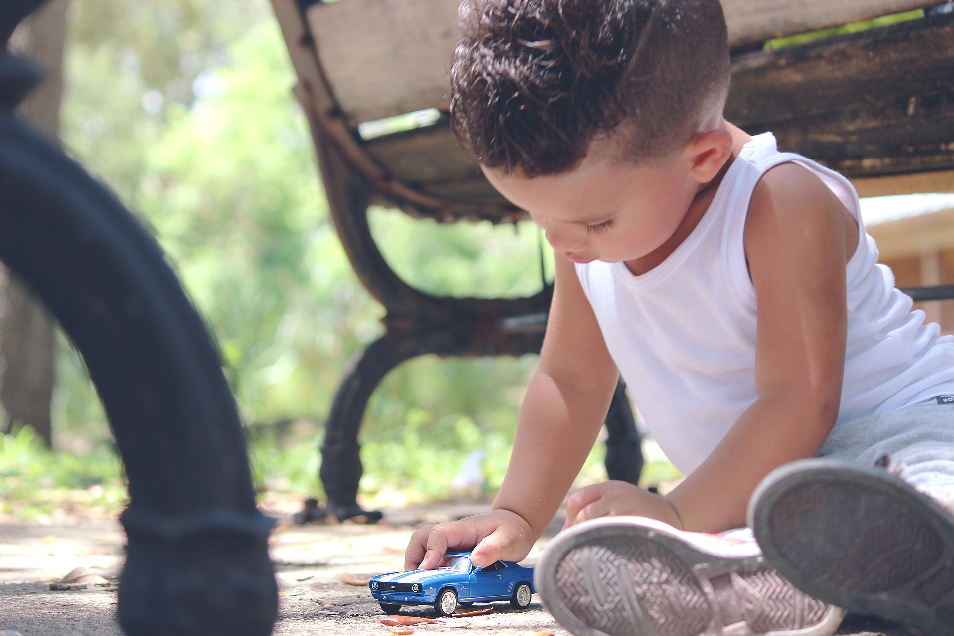 Boy Playing with Car by Bench